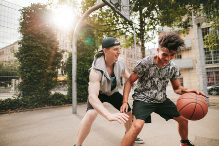 Two young friends playing basketball on court outdoors