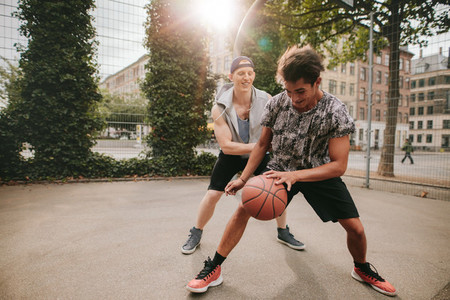 Friends playing basketball on court and having fun