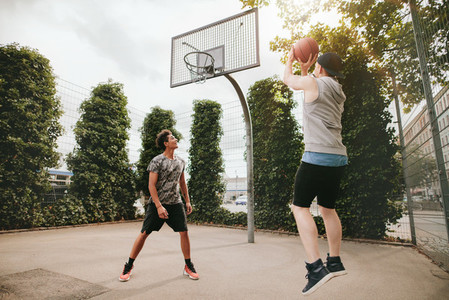 Two friends playing basketball on court