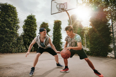 Two young men having a game of basketball