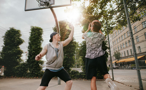 Teenage friends playing a game of basketball