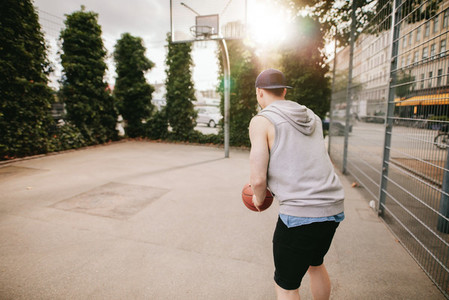 Young guy playing basketball on outdoor court