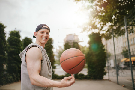 Smiling streetball player spinning the ball