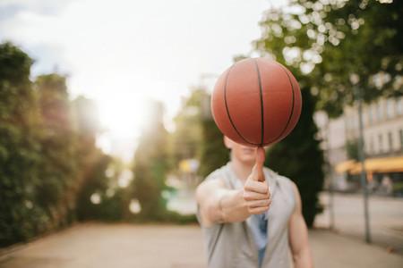 Man balancing basketball on his thumb