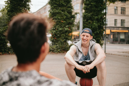 Two friends relaxing after playing basketball on court