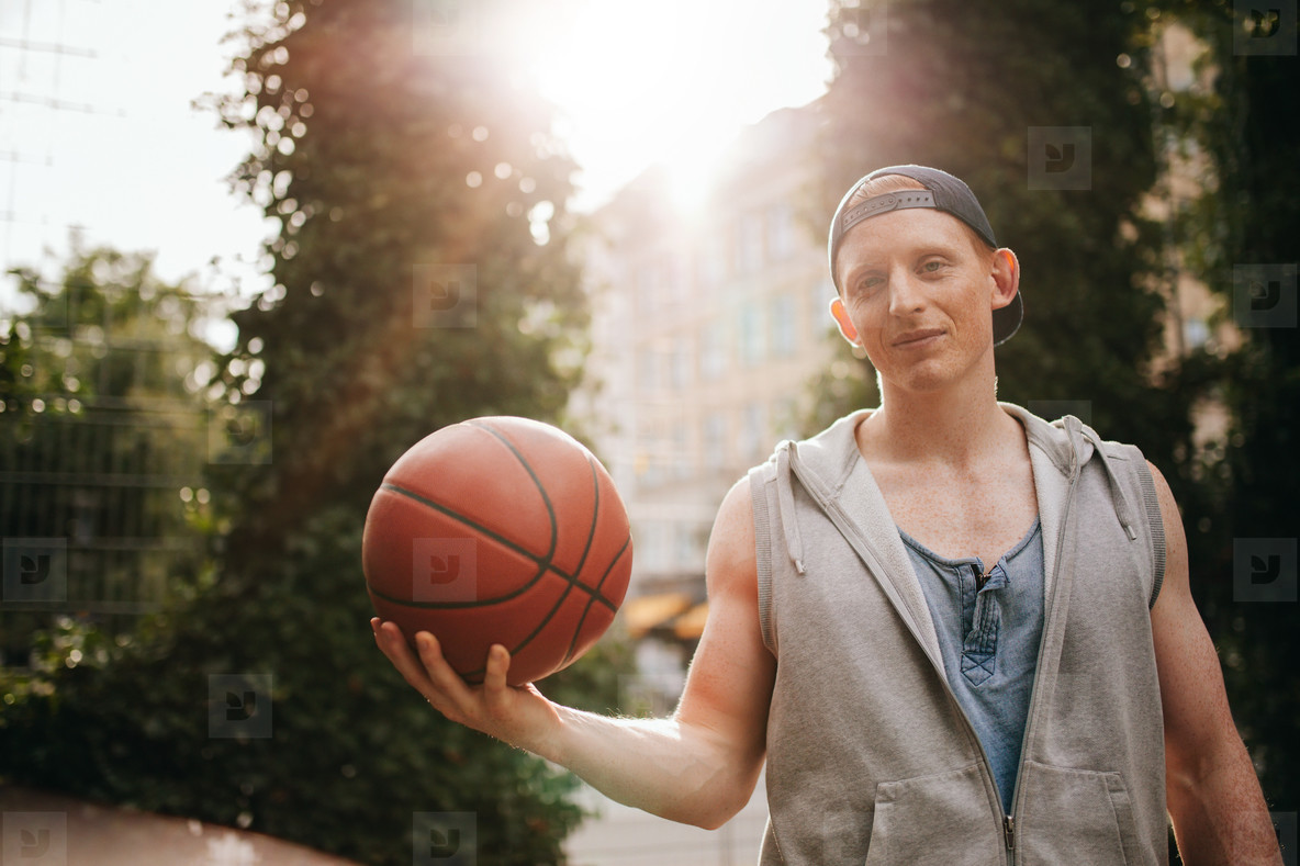 Teenage streetball player with a ball in hand