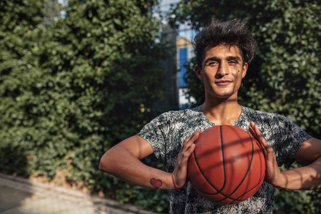 Young basketball player holding a ball on outdoor court
