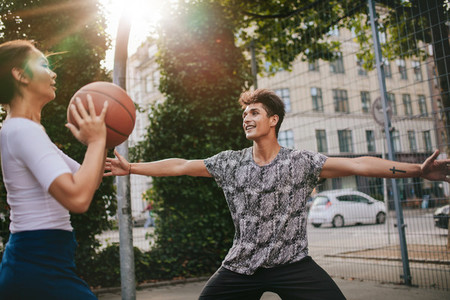 Teenage friends playing streetball against each other