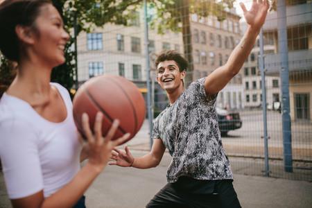 Streetball players on court playing basketball