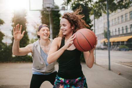 Teenage friends enjoying a game of streetball