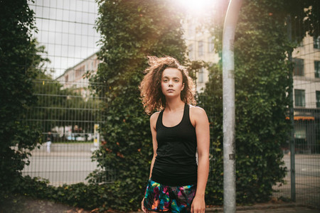 Beautiful young girl standing on basketball court