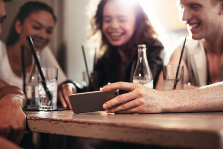 Friends in a bar watching funny video on mobile phone