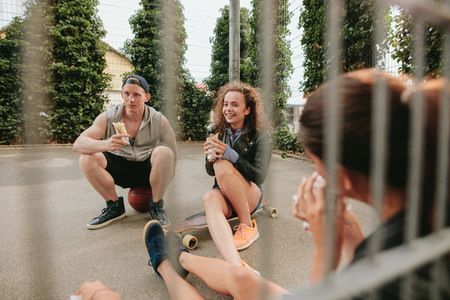 Group of friends sitting at basketball court and having fun