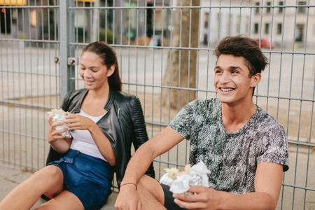 Young man and woman sitting outdoors and smiling
