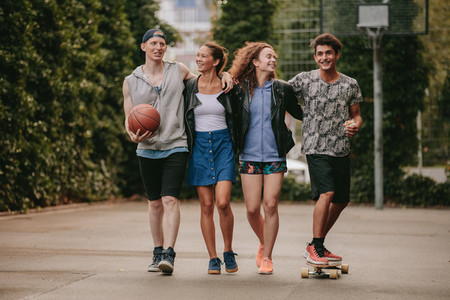 Young friends walking with skateboard and basketball