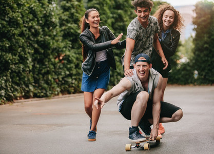 Group of teenagers enjoying outdoors with skateboard