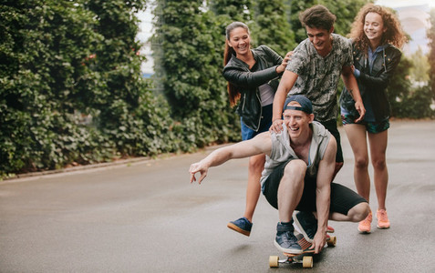Group of friends having fun outdoors with skateboard