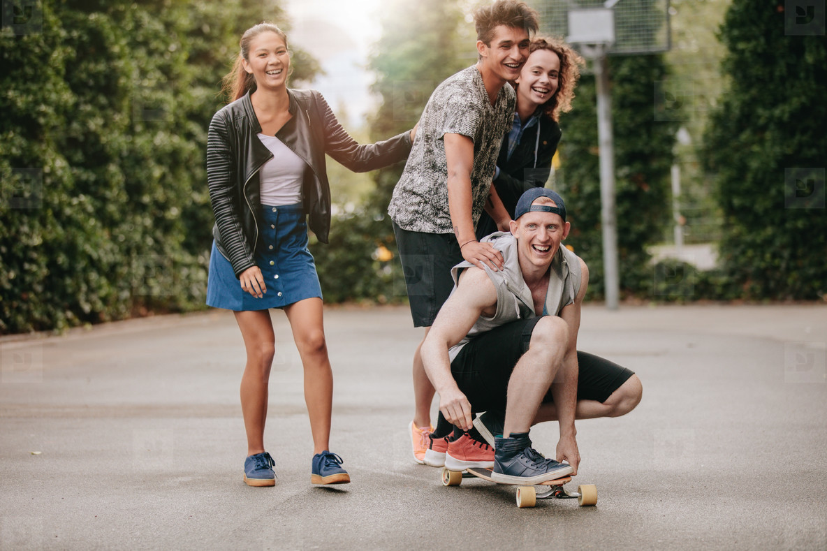 Teenage guys on skateboard with girls