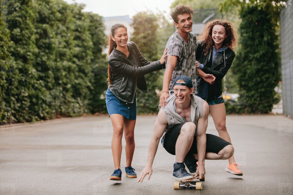 Four teenagers enjoying outdoors with skateboard