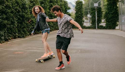 Woman skating on a basketball court with friend