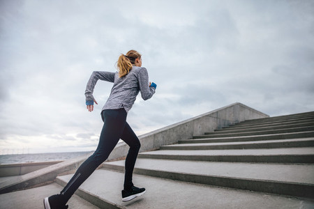 Fit young woman running on steps