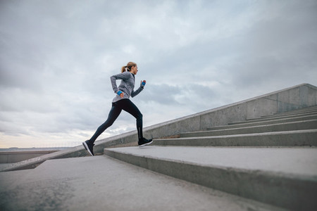 Woman running on steps outdoors