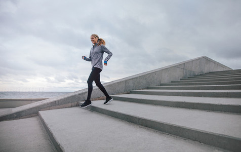 Healthy young woman running down on steps