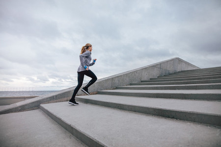 Healthy woman climbing up on stairs
