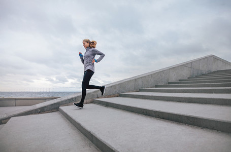 Healthy sports woman running down the stairs