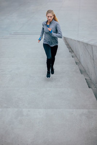 Young sport woman running upstairs