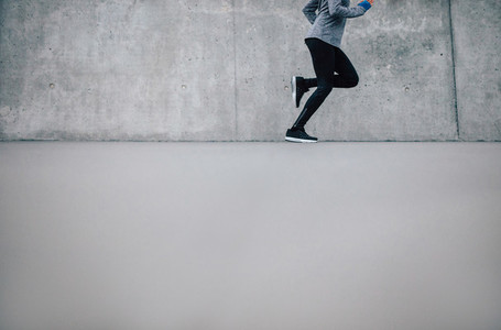 Female runner running on gray background