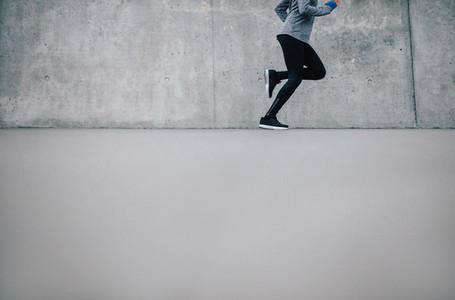Female runner running on gray background