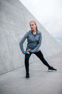 Female runner doing stretches in city