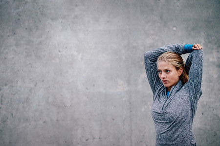 Female runner stretching arms after a running session
