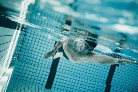 Professional male swimmer inside swimming pool