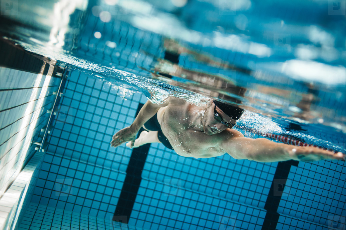 Young man swimming the front crawl in a pool