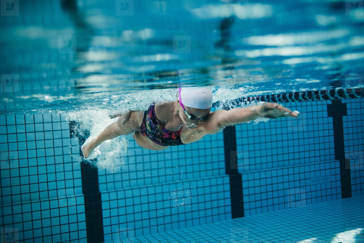 Female swimmer in action inside swimming pool