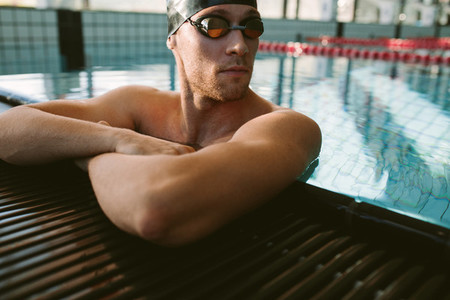 Pro male swimmer relaxing at pool edge