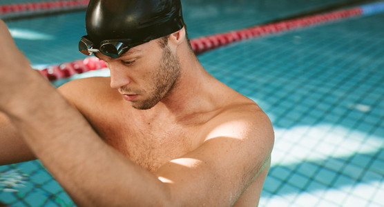 Professional male athlete resting on the edge of pool