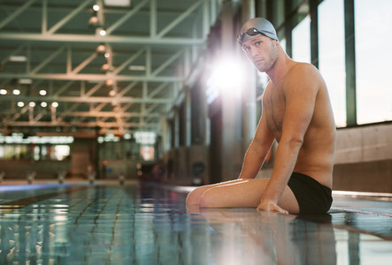 Male swimmer relaxing at the edge of a pool