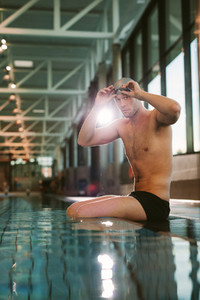 Professional male swimmer sitting on edge of a pool