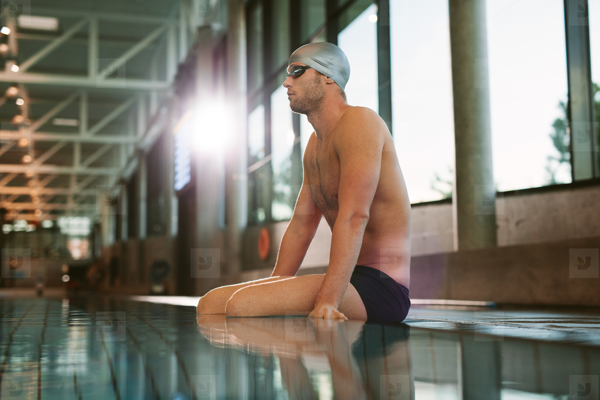 Male swimmer relaxing at the edge of a swimming pool