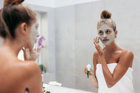 Beautiful woman applying mask to her face