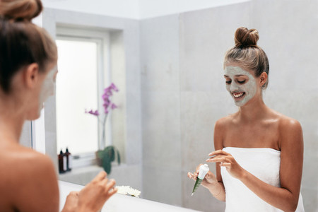 Young woman applying face mask in bathroom