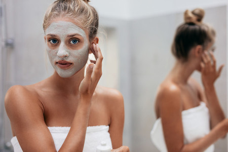 Woman applying facial mask in bathroom