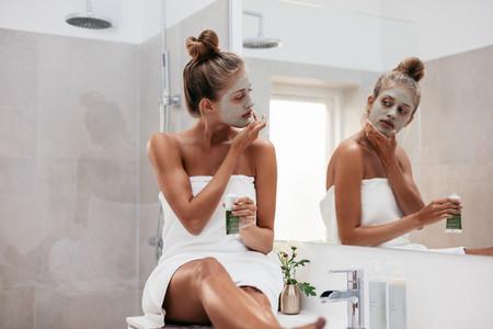 Young woman in bathroom applying facepack