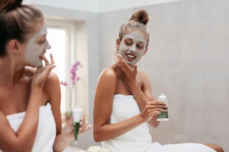 Young woman applying facepack in bathroom