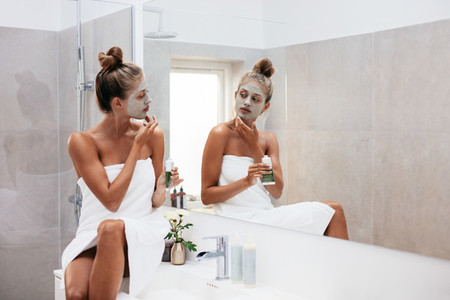 Woman applying facial mud clay mask