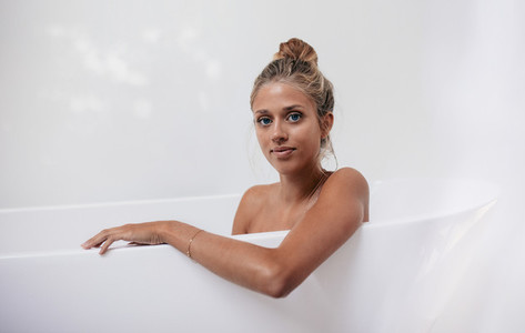 Young female sitting in bathtub
