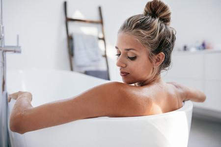 Young woman bathing in bathtub
